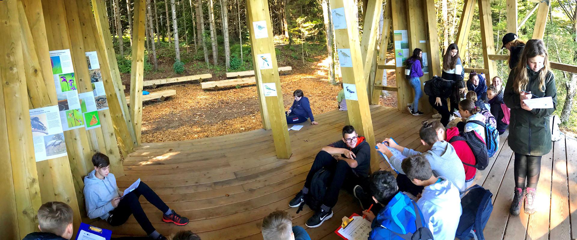 Opazovalnica Kuharca pod streho zlahka sprejme za ves razred učencev, kar smo za reševanje učnih listov izkoristili tudi mi, saj so bile klopi zunaj še mokre. Ob enkratnem razgledu na polno jezero z obronka javorniškega gozda smo spoznavali pomen tega svetovnega jezerskega fenomena in prebivalce, ki naseljujejo gozdove ob njem.